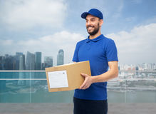 Happy delivery man with box over singapore city Royalty Free Stock Photo