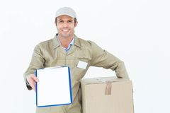 Happy delivery man with box showing clipboard Stock Photography