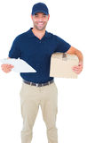 Happy delivery man with cardboard box and clipboard Royalty Free Stock Image