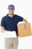 Happy delivery man with cardboard box and clipboard Royalty Free Stock Photo