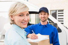 Happy delivery man with customer. Happy delivery men with customer outside the warehouse stock images