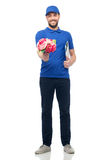 Happy delivery man with flowers and clipboard Royalty Free Stock Photo