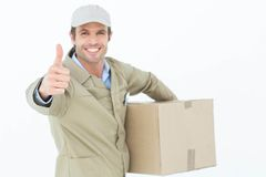 Happy delivery man gesturing thumbs up while carrying box Royalty Free Stock Images