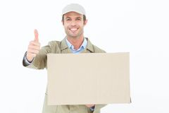 Happy delivery man gesturing thumbs up while carrying cardboard box Royalty Free Stock Image