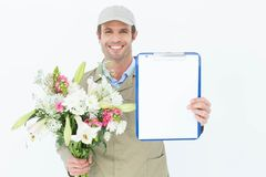 Happy delivery man holding bouquet and clipboard Stock Photo