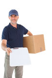 Happy delivery man holding cardboard box and clipboard Stock Photos
