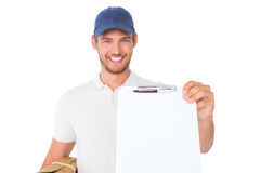 Happy delivery man holding cardboard box and clipboard stock photo
