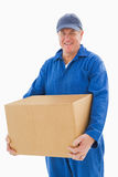 Happy delivery man holding cardboard box Stock Images