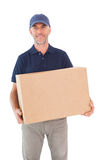 Happy delivery man holding cardboard box Royalty Free Stock Photography