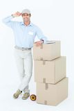 Happy delivery man leaning on stacked cardboard boxes Stock Image