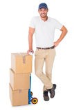 Happy delivery man leaning on trolley of boxes Stock Photos