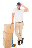 Happy delivery man leaning on trolley of boxes. On white background Stock Photos