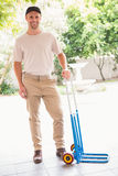Happy delivery man leaning on trolley. Outside the warehouse Royalty Free Stock Image