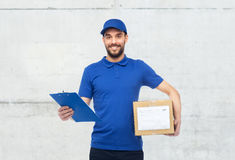 Happy delivery man with parcel box and clipboard. Delivery service, mail, logistics, people and shipping concept - happy man with parcel box and clipboard over royalty free stock image