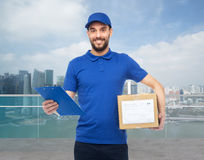 Happy delivery man with parcel box and clipboard Stock Photos
