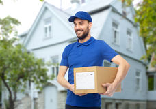 Happy delivery man with parcel box over house Royalty Free Stock Photos