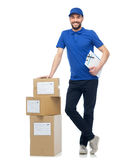 Happy delivery man with parcel boxes and clipboard Stock Photography