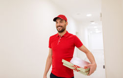 Happy delivery man with pizza boxes in corridor Stock Image