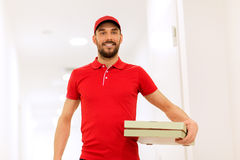 Happy delivery man with pizza boxes in corridor Royalty Free Stock Images