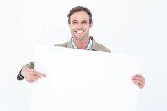 Happy delivery man pointing at blank billboard Royalty Free Stock Image