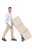 Happy delivery man pushing trolley of boxes Royalty Free Stock Photos