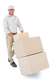 Happy delivery man pushing trolley of boxes Stock Photography