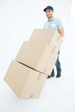Happy delivery man pushing trolley of boxes Royalty Free Stock Photography