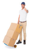 Happy delivery man pushing trolley of boxes. On white background Royalty Free Stock Images