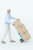 Happy delivery man pushing trolley of cardboard boxes Stock Images