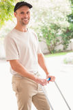 Happy delivery man pushing trolley. Outside the warehouse Royalty Free Stock Images