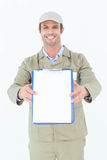 Happy delivery man showing blank paper on clipboard Royalty Free Stock Photo