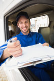 Happy delivery man showing clipboard to sign to customer Royalty Free Stock Photos