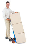 Happy delivery man with trolley of boxes Royalty Free Stock Images