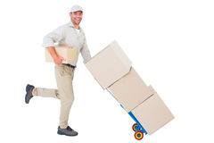 Happy delivery man with trolley of boxes running on white background Stock Photography