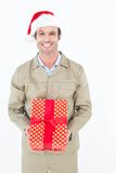 Happy delivery man wearing Santa hat while holding gift. Portrait of happy delivery man wearing Santa hat while holding gift on white background Stock Photos