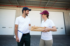 Happy delivery man and woman standing with clipboard and parcel Stock Photo
