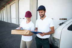 Happy delivery man and woman writing on clipboard next to van Royalty Free Stock Photography