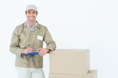 Happy delivery man writing on clipboard by cardboard boxes Stock Photos