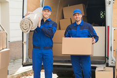 Happy Delivery Men Carrying Cardboard Box And Carpet. Portrait of happy delivery men carrying cardboard box and carpet outside van royalty free stock photos