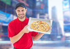 Happy deliveryman with pizza in the city with lights. Digital composite of Happy deliveryman with pizza in the city with lights Royalty Free Stock Photos