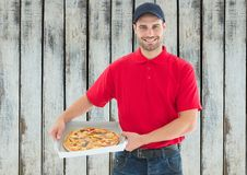 Happy deliveryman with pizza. Wood background Stock Images
