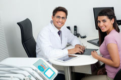 Happy Dentist And Patient At Office Desk Stock Image