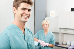 Happy Dentist Portrait. Portrait of male dentist with female assistant standing at dental clinic stock photo
