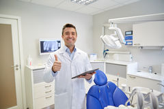 Happy dentist showing thumbs up with tablet pc Stock Photo