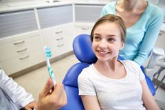 Happy dentist showing toothbrush to patient girl Stock Photos