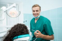 Happy dentist smiling at his dental office Royalty Free Stock Photography