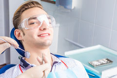 Happy dentistry. A handsome young guy sits satisfied in an armchair by a dentist. Successful dentistry. Happy patient stock image