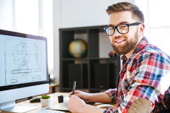 Happy designer drawing blueprint on computer using pen tablet. Portrait of happy handsome modern designer drawing blueprint on computer using pen tablet with royalty free stock photography