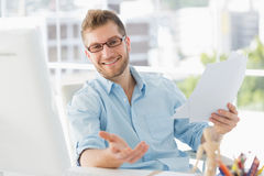 Happy designer sitting at his desk gesturing at camera Stock Image