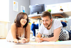Happy designers working on a document with colleagues working Stock Photography